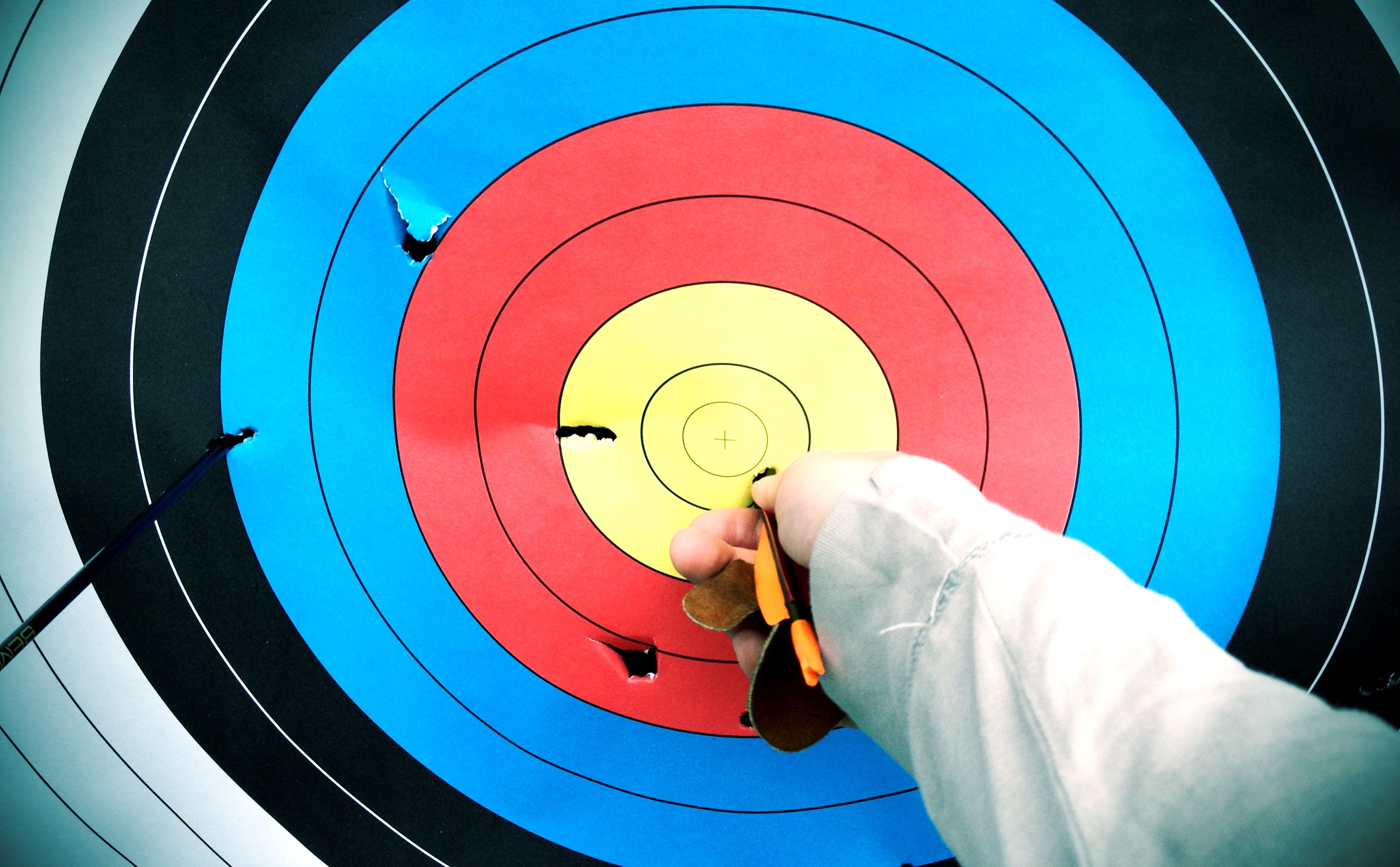 pulling an arrow out of an archery target